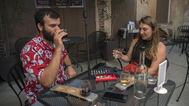 Ramin Rostampour, left, and Ramie Taylor enjoy a board game and some wine at the Jeremy Wine Company in downtown Lodi on Saturday. Under new guidance from the county, wineries are permitted to reopen with modifications aimed to help ensure safety for customers and workers during the coronavirus pandemic.