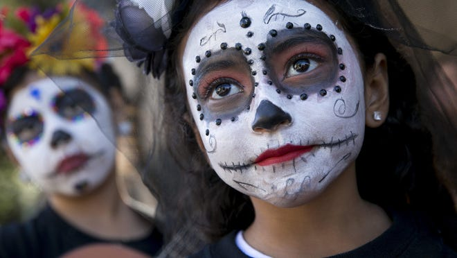 Natalie Mandujano, left, and America Lara wait for the start of the grand procession at the Viva la Vida festival and parade in downtown Austin in 2018. This year's festivities have moved online.