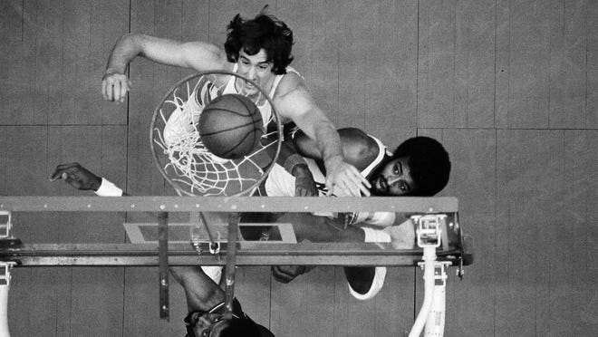 """Freeport native Kim Hughes, top center, of the New Jersey Nets, positions himself for a rebound as Philadelphia 76ers star Julius """"Dr. J"""" Erving, bottom, watches his shot go through the net in a March 20, 1977 game."""