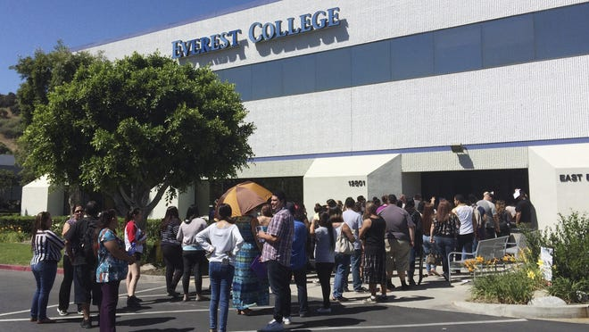 In this April 28, 2015, file photo, students wait outside Everest College in Industry, Calif., hoping to get their transcriptions and information on loan forgiveness and transferring credits to other schools. Corinthian Colleges shut down all of its remaining 28 ground campuses on April 27, 2015, displacing 16,000 students.