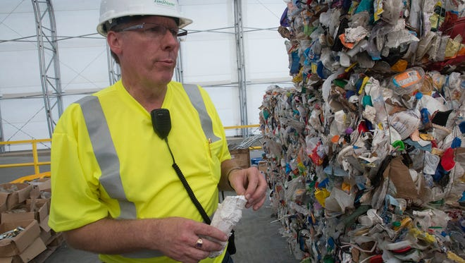 Zero Waste Operations Director Mark Buntjer pulls a piece of packing material from a bundle of recycled material at the Emerald Coast Utilities Authority recycling facility. The city of Pensacola is in negotiations with ECUA to begin using its recycling center.
