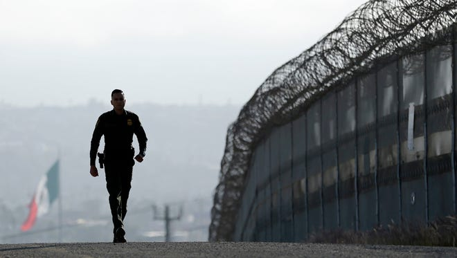 In this June 22, 2016, photo, Border Patrol agent Eduardo Olmos walks near the secondary fence separating Tijuana, Mexico, background, and San Diego in San Diego. U.S. immigration authorities caught barely half the people who illegally entered the country from Mexico last year, according to an internal Department of Homeland Security report that offers one of the most detailed assessments of U.S. border security ever compiled. The report found far fewer people are attempting to get into the U.S. than a decade ago and that 54 percent of those who tried were caught in the year ending Sept. 30, 2015.
