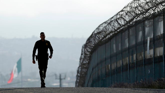 In this June 22, 2016 file photo, Border Patrol agent Eduardo Olmos walks near the secondary fence separating Tijuana, Mexico, background, and San Diego in San Diego.