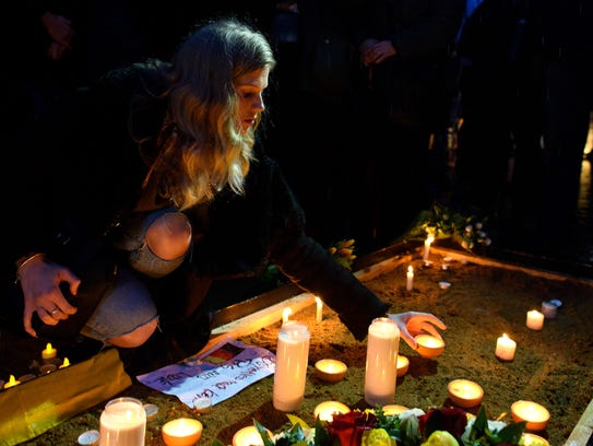 A mourner lights a candle in Trafalgar Square in London