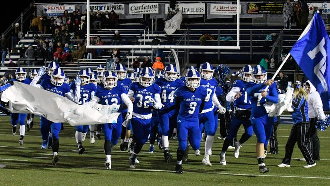 Harper Creek football players take the field before Friday night's match against East Lansing.