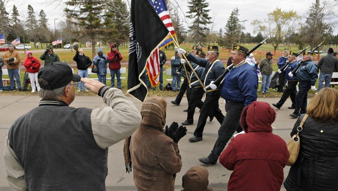 People along the route clap and salute as a color guard passes during the 2014 Veterans Day Parade at the St. Cloud VA Health Care System.