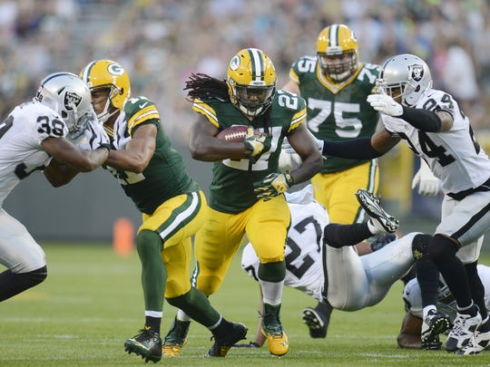 Green Bay Packers running back Eddie Lacy (27) runs against the Oakland Raiders Charles Woodson (21) in an exhibition game at Lambeau Field in Green Bay, Wis. on Friday, Aug. 22, 2014. Kyle Bursaw / Press-Gazette Media