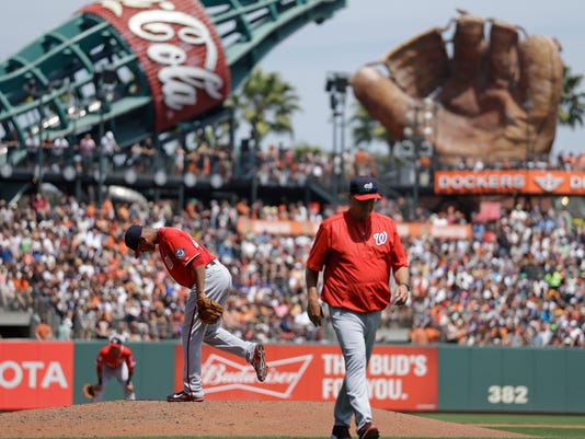 Washington Nationals pitcher Joe Ross, second from right, kicks the mound after speaking with pitching coach Steve McCatty, right, in the fourth inning of a baseball game against the San Francisco Giants, Sunday, Aug. 16, 2015, in San Francisco. (AP Photo/Ben Margot)