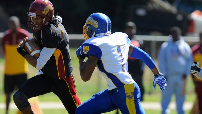 Tuskegee quarterback Kevin Lacey is chased by Fort Valley State's Brian Walker in Tuskegee, Ala. on Saturday October 4, 2014.
