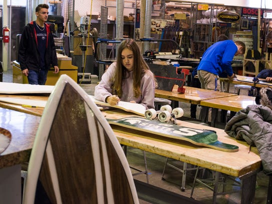 Kylee Culm 16, sketches a design on her longboard as