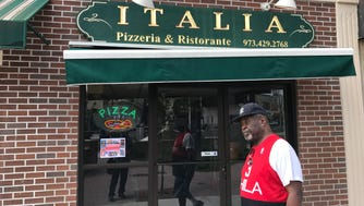 A man walks past Italia Pizza in Bloomfield on Tuesday, June 27, 2017.