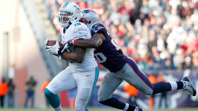 Miami Dolphins wide receiver Rishard Matthews (18) is tackled by New England Patriots cornerback Logan Ryan (26) during the fourth quarter at Gillette Stadium.