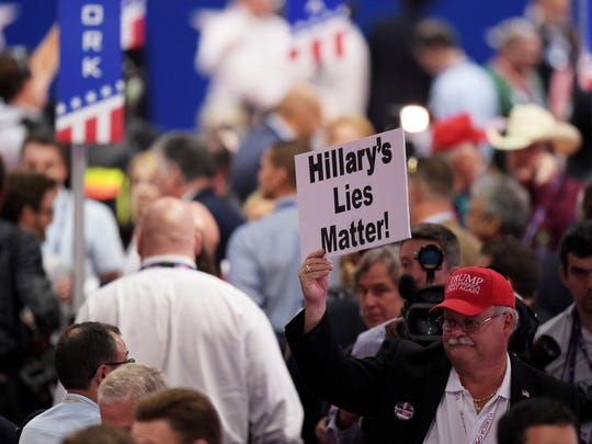 "A delegate holds up a sign that reads ""Hillary's Lies"