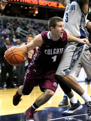 Colgate Raiders guard Austin Tillotson is defended by Georgetown Hoyas forward Mikael Hopkins during a game at the Verizon Center in December 2013.