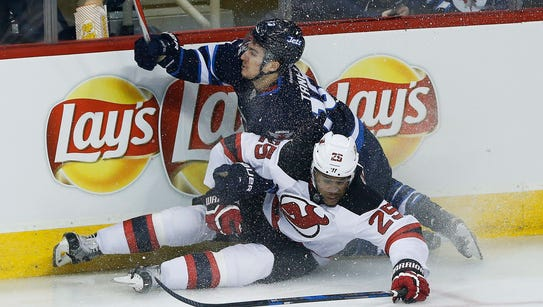 Winnipeg Jets' Brandon Tanev (13) and New Jersey Devils'