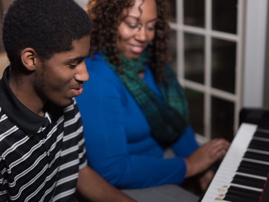 Steven Jones plays the piano for his mother, Chandra Jones