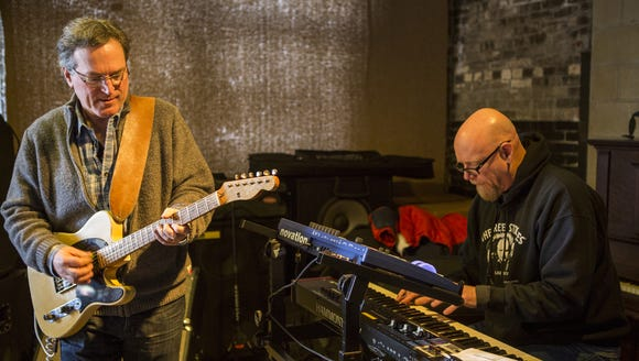 Kevin Walsh, left, plays the guitar while Dan Long