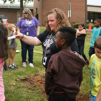 Moore Magnet Elementary second graders look at the magnolia sapling they are planting during their Arbor Day celebration on Friday.