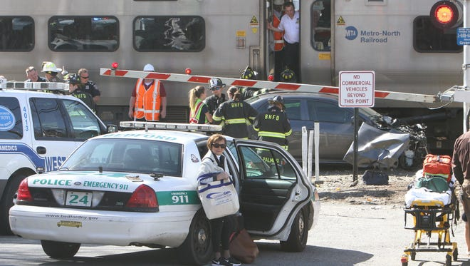 A woman named Audrey Hefner stand near a Bedford police car after the car that she was a passenger in was struck by a northbound MetroNorth train at the Green Lane crossing in Bedford Hills April 27, 2016. Neither Audrey or the person driving the car were injured.