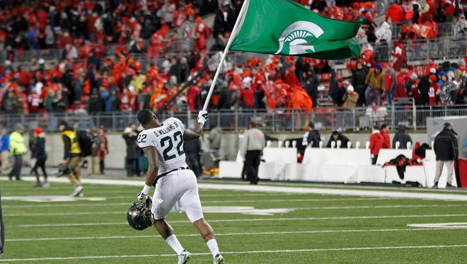 Michigan State Spartans running back Delton Williams (22) celebrates with a school flag after the Spartans' game against the Ohio State Buckeyes at Ohio Stadium.
