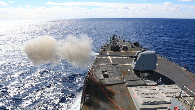 The Arleigh Burke-class guided-missile destroyer USS McCampbell fires a MK 45 5-inch lightweight gun in the Indo-Asia-Pacific region during a live-fire exercise in this Jan. 17, 2016, file photo.