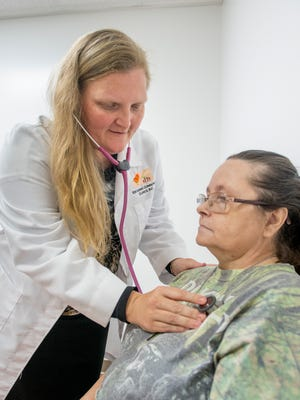 Family Nurse PractitionerPaula Kennedy, left, listens to Karen Brazwell's heart at the new Escambia Community Clinic in Century on Wednesday, Aug. 9, 2017. The clinic is sharing the building with the previously established Lakeview Center in Century.