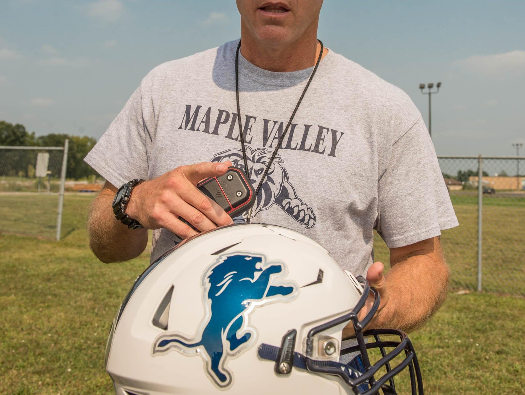Maple Valley head coach Marty Martin shows off the program's new helmet with sensors built in to help avoid concussions .