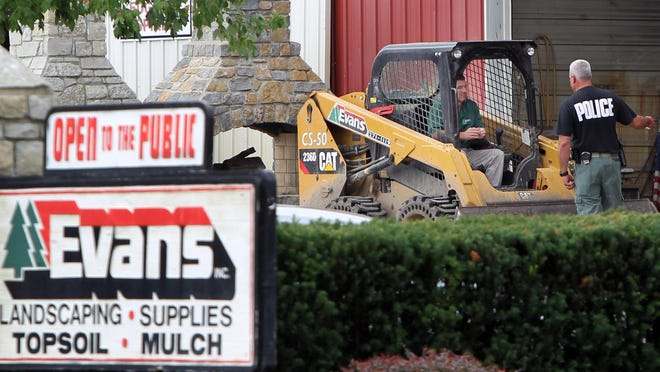 A police officer talks to an equipment operator at Evans Landscaping's Newton facility. The landscaping company raided by FBI agents is enmeshed in a lawsuit alleging fraud involving a contract with a minority-owned business on public projects.