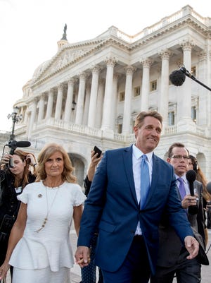 Sen. Jeff Flake, R-Ariz., accompanied by his wife Cheryl, leaves the Capitol in Washington, Oct. 24, 2017, after announcing he won't seek re-election in 2018.