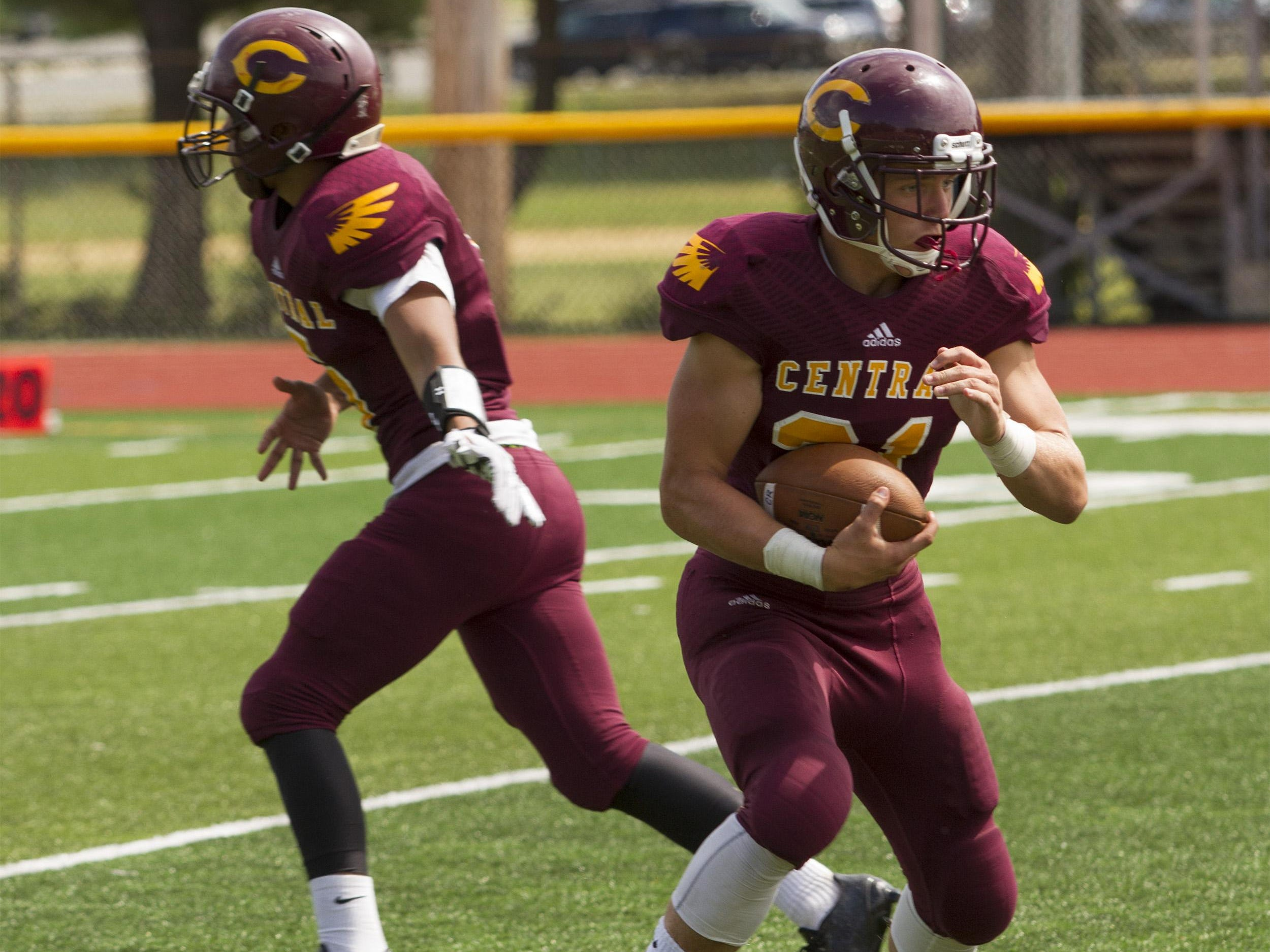Central running back Mike Bickford takes a handoff from quarterback Mike Miserendino.