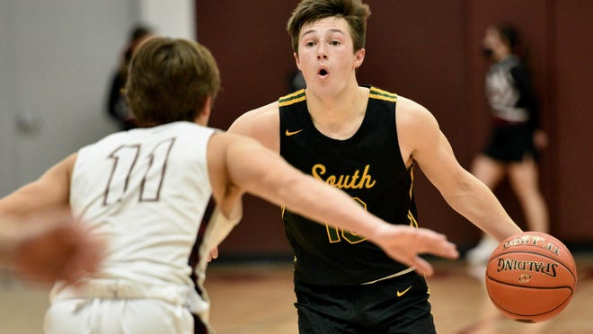 Salina South's Devon Junghans (10) sets up a play while being defended by Salina Central's Logan Losey (11) during Friday's game at the Central gym.