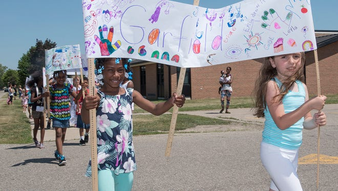 Avielle Carey and Erisa Telias hang onto their banner in a strong wind during Monday's parade at Garfield Elementary. Garfield, which is closing as an elementary this year, has traditionally marked the end of the school year with a parade.
