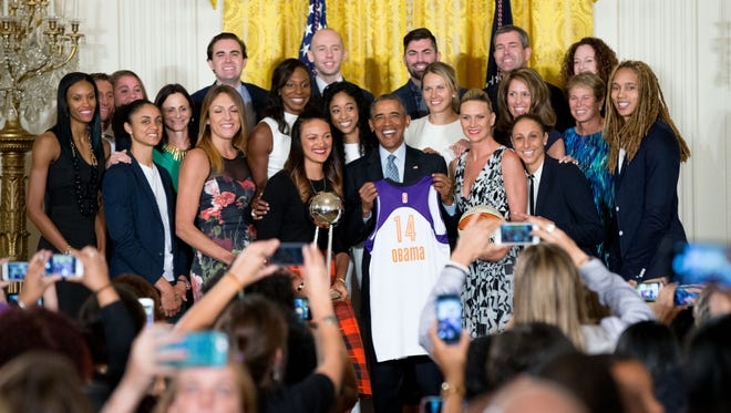 President Barack Obama poses with the Mercury in the East Room of the White House.
