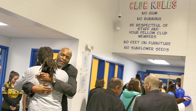 Reggie Smith, gym coordinator at the Boys & Girls Club of Rochester, gets a warm hug from Shawn Brown, from Teen Empowerment, at the club's expansion unveiling Thursday, March 10, 2016 on Genesee Street in Rochester.
