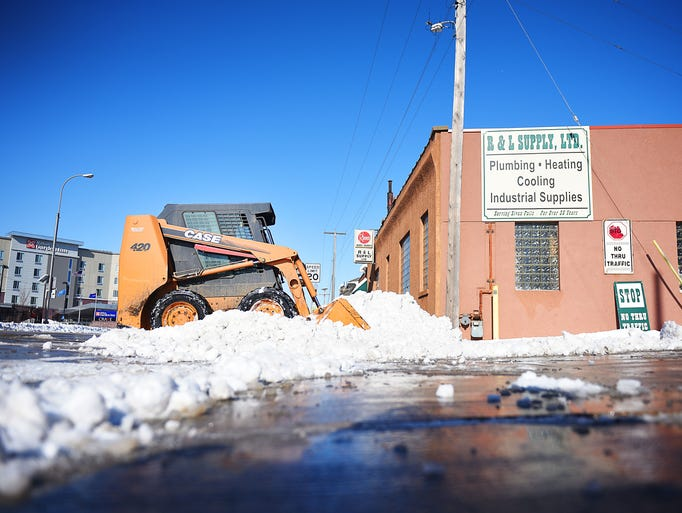 Gary Arens clears snow from the R & L Supply parking