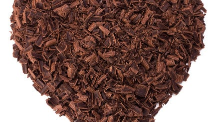Large heart made of grated chocolate against white back