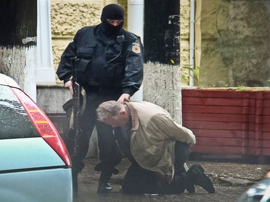 "In this June 27, 2011 photo provided by the Moldova General Police Inspectorate, Teodor Chetrus is detained by a police officer in Chisinau, Moldova during a uranium-235 sting operation. In many of the smuggling cases in this former Soviet republic, ringleaders insulated themselves through a complex network of middlemen to shield the bosses from arrest. In this case, Chetrus was the go-between. Former Moldova Police investigator Constantin Malic recalls that Chetrus said, ""I really want an Islamic buyer because they will bomb the Americans."""
