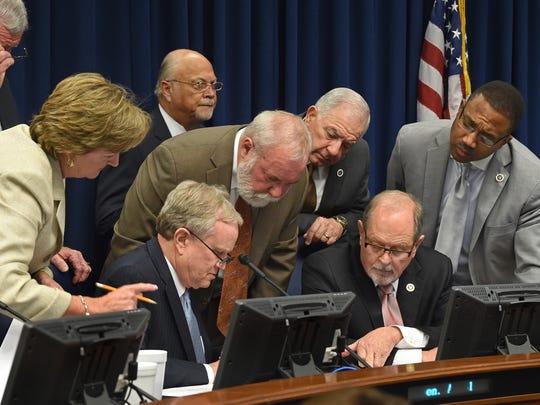 State Senate Finance Committee members gather around