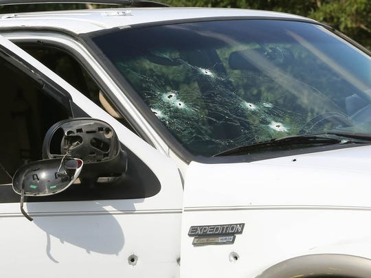 Police investigate a vehicle involved in a shooting in Egg Harbor Township, N.J., Monday Aug. 29, 2016. A deadly shootout on a New Jersey highway left multiple injured.