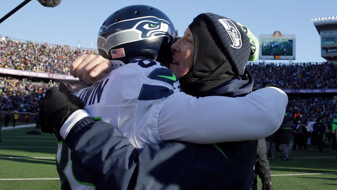 Seattle Seahawks head coach Pete Carroll celebrates with wide receiver Doug Baldwin (89) after an NFL wild-card football game, Sunday, Jan. 10, 2016, in Minneapolis. The Seahawks won 10-9.