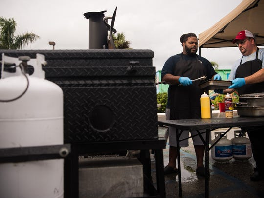 """Chef Tavoris Ingram (left) transfers chicken, mahi and tuna to cook Robert Dery, both Port St. Lucie, after cooking the proteins using propane outside of the Twisted Tuna on Monday, Jan. 8, 2018, in Port Salerno. """"Everything else is in the kitchen, we're just cooking all the protein out here,"""" Ingram said, referring to the food preparation. The restaurant, and several other businesses in the area, lost gas service after a line was ruptured in Martin County earlier in the day."""