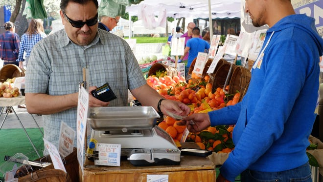 A shopper pays for his produce at a farmers market in downtown Los Angeles.
