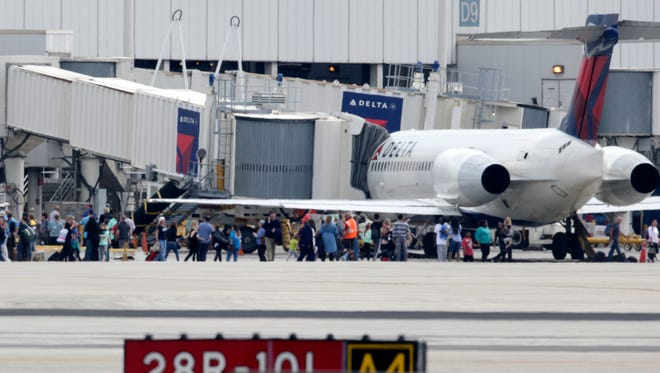 People stand on the tarmac at the Fort Lauderdale-Hollywood International Airport, Friday.