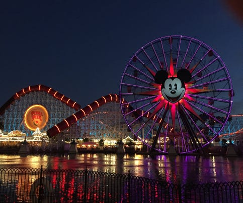 The Incredicoaster and Mickey's Fun Wheel at Disney California Adventure lit up at night.
