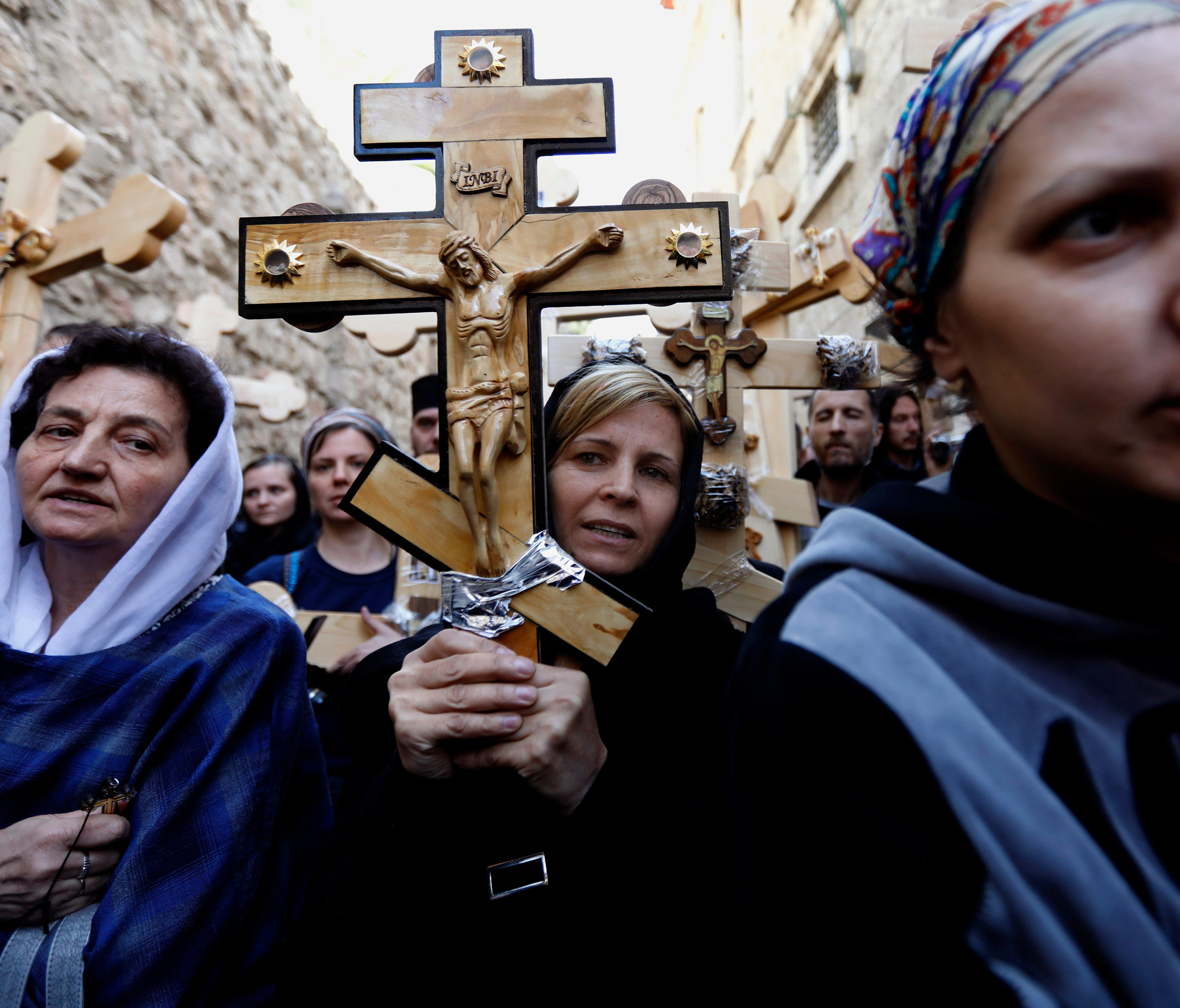 Christian pilgrims carry wooden crosses along the path where Jesus walked, now known as the