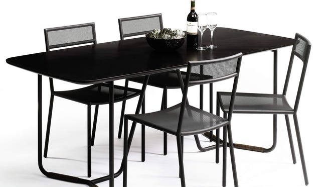 The Boot Leg dining table pairs a charcoal-black finish with leather-wrapped legs.