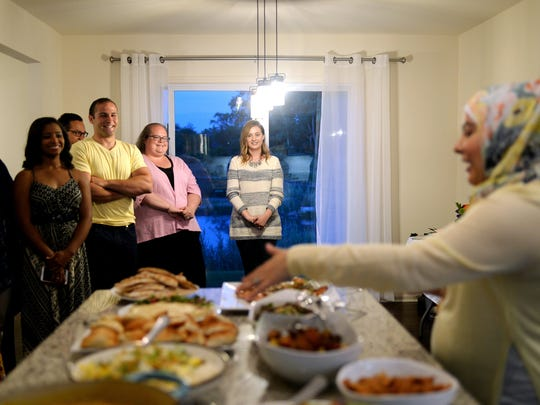 "Center from left, Mohamed Fakih, of Dearborn Heights, Aimee Twarek, and Lauren Schleicher, both of Berkley, smile next to other guests as Amanda Saab, right, describes the menu during ""Dinner with Your Muslim Neighbor"" on Sunday, June 11, 2017 at Saab's home in New Boston."