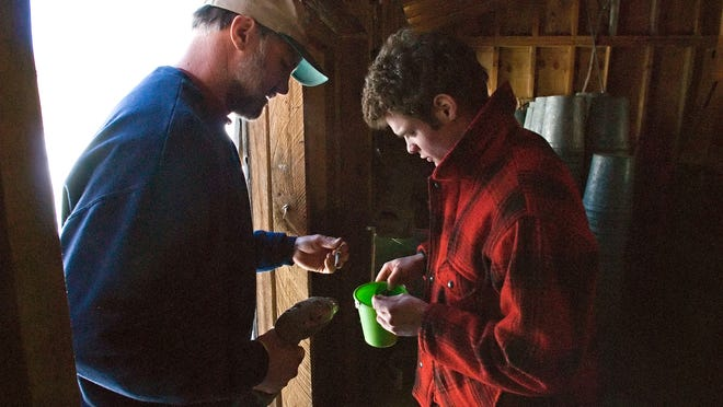 Ben Gates, right, and his father, Jonathan, look for sap spouts before tapping maples at the Gates farm in Franklin in mid-March, 2008.