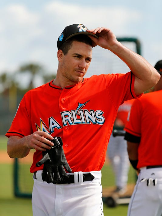 FILE - In this Feb. 18, 2018, file photo, Miami Marlins catcher J.T. Realmuto prepares to step into the batting cage during spring training baseball practice in Jupiter, Fla. (AP Photo/Jeff Roberson, File)
