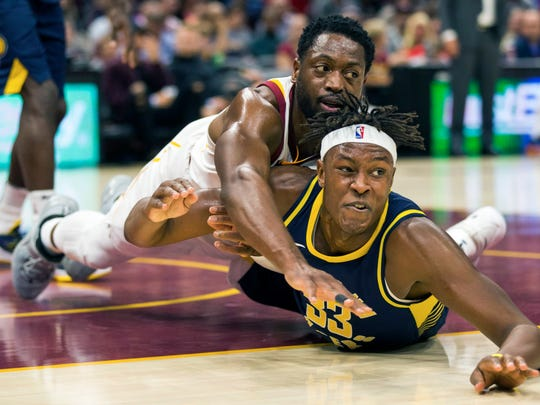 Cleveland Cavaliers' Dwyane Wade, left, falls on Indiana Pacers' Myles Turner while battling for a loose ball during the first quarter of an NBA preseason basketball game, Friday, Oct. 6, 2017, in Cleveland.